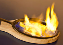 Halloumi cheese on fire in a skillet